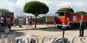 Un momento de la intervención de los bomberos voluntarios de La Bañeza en el incendio del solar.