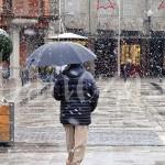 Un viandante cruza la Plaza Mayor de La Bañeza mientras está nevando.